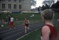 "Augsburg women's track and field team runner ""Cheryl"" running with a baton, April 1977"