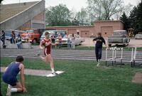 "Augsburg women's track and field team runner ""Connie"" performing a high jump, April 1977"