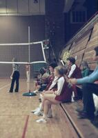 Augsburg women's volleyball team and coach sitting on the bleachers, January 1977