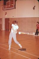 An Augsburg women's softball team player practicing hitting the ball, April 1975