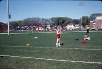 "Augsburg women's track and field team runner ""Karen"" standing with a javelin, April 1977"