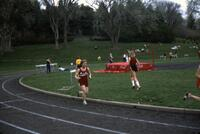 "Augsburg women's track and field team runner ""Cheryl"" running past a curve, April 1977"
