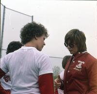 An Augsburg women's softball team player conversing with a coach, April 1975