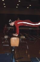 An Augsburg women's gymnastics team member raising herself on a hurdle, February 1977