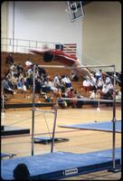 An Augsburg women's gymnastics team member flipping from a low bar over a high bar, March 1979