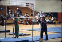 An Augsburg women's gymnastics coach and a rival coach helping set up a low bar, March 1979