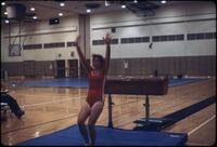 "An Augsburg women's gymnastics team member doing a ""Ta-Da"" stance after vaulting a hurdle, March 1979"