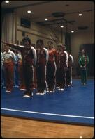 Augsburg women's gymnastics team lined up on a mat with other teams, March 1979