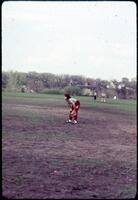 An Augsburg women's softball team player in the outer field taking a break, April 1977