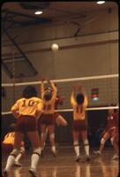 An Augsburg women's volleyball team player jumping to stop an incoming volleyball, November 1978