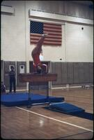 An Augsburg women's gymnastics team member holding a handstand on a hurdle, March 1979