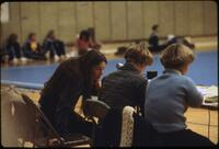 A panel of judges writes notes on a gymnastics routine, March 1979