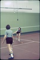 An Augsburg women's tennis team player swinging her racket in practice, April 1977