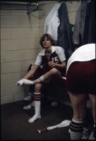 An Augsburg women's basketball team player taking off her socks, circa 1979