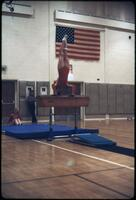 An Augsburg women's gymnastics team member holding a handstand on top of a hurdle, March 1979