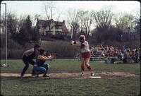 An Augsburg women's softball team player standing at home base during a game, April 1977