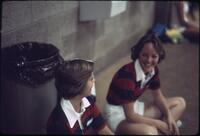 Augsburg women's tennis team players conversing while sitting near the wall, April 1977