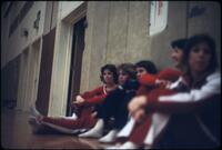 Augsburg women's gymnastics team laying against the wall of the gym, March 1979