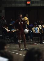 An Augsburg women's volleyball team player standing with a volleyball at the edge of the court, November 1978