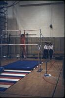 An Augsburg women's gymnastics team member hanging on a high bar, March 1979