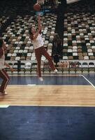 An Augsburg women's basketball team player jumping for a layup, circa 1978