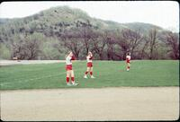 Augsburg women's softball team standing on the field in uniform, April 1977