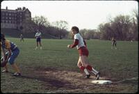 An Augsburg women's softball team player standing with one foot on a base, April 1977