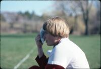 An Augsburg women's softball team player icing her face, April 1978