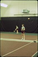 Augsburg women's tennis team players practicing serving, April 1977