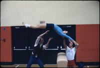 An Augsburg women's gymnastics team member getting guided by two people as she flips, March 1978