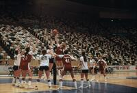 An Augsburg women's basketball team player from each team competing in a toss up, circa 1979