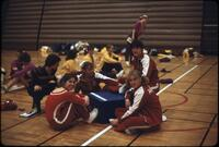 Women's gymnastics team and other competing teams sitting on the ground, March 1979