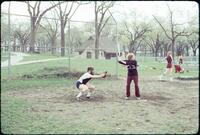 An Augsburg women's softball team player hitting at home base, April 1977