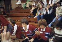 Women's volleyball coach sitting with her players, November 1977
