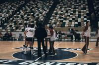 An Augsburg women's basketball team players from each team standing at the center court, circa 1979