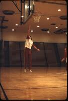 An Augsburg women's basketball team member jumping and reaching toward a rim, March 1979