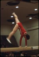 An Augsburg women's gymnastics team member mid handstand on top of a balancing beam, March 1979