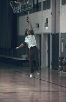 An Augsburg women's basketball team player doing a layup, February 1978
