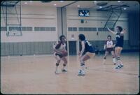 An Augsburg women's basketball team player trying to pass while guarded, February 1978