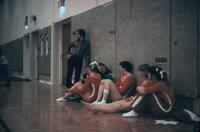 Women's gymnastics team laying on the gym wall, circa 1978