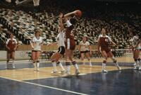 An Augsburg women's basketball team player jumping to the ball, circa 1978