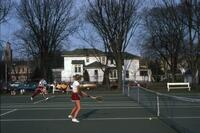 An Augsburg women's tennis team player walking up to the tennis court in Winona, circa 1979