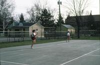 Augsburg women's tennis team players standing in position in two volleyball courts, circa 1979