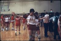 An Augsburg women's basketball player smiling and walking off the basketball court, February 1980