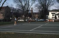 An Augsburg women's tennis team player raising her racket to serve the ball, circa 1979