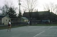 An Augsburg women's tennis team player watching a team member strike the tennis ball, circa 1979