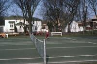 An Augsburg women's tennis team player running forward on a tennis court in Winona, circa 1979