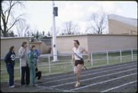 An Augsburg men's track and field team runner runs across the finish line, 1982.