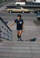 An Augsburg women's volleyball team player dressed in blue climbing the stairs, circa 1978