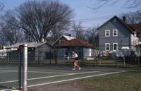 An Augsburg women's tennis team player swinging her racket to return the tennis ball, circa 1979